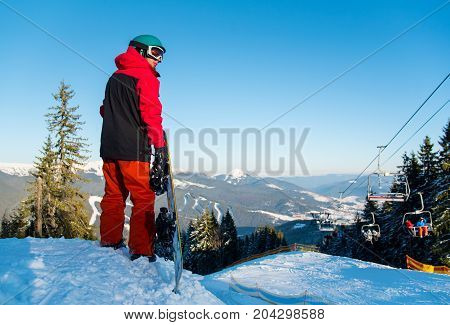 Rear View Shot Of A Male Snowboarder Looking Around, Enjoying Beautiful Winter Evening. Mountains, F