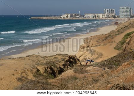 Herzliya, Israel - 20 october 2017: Two serfers go to beautiful sea with waves and sky