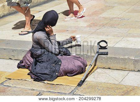 Poor woman begging in the street in Europe