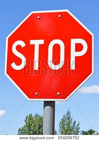 Stop sign at the road crossing against sky