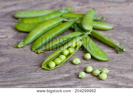 Green peas on wooden background, ripe Green peas isolated on white background