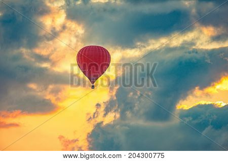 Red hot air balloon flying in beautiful sky during sunrise.