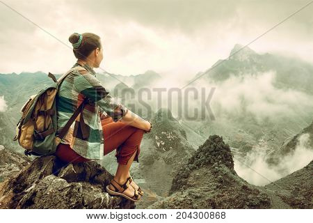 Hiker in mountains enjoying on view of foggy valley in mountains. Mountains landscape travel to Asia happiness emotion summer hike concept.