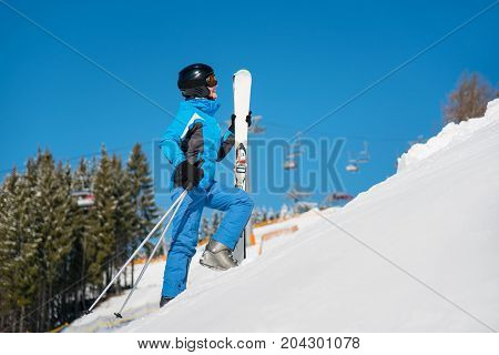 Female Skier Walking Up The Slope In The Mountains Carrying Her Skis At Winter Resort Copyspace