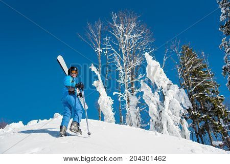 Low Angle Shot Of A Happy Female Skier In Winter Sportswear Carrying Her Skis On The Shoulder While