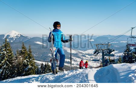 Full Length Shot Of A Woman Skier In Winter Sportswear Standing On Top Of A Mountain With Her Skis A
