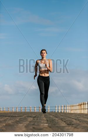 Fitness Woman Running On The Seaside Promenade