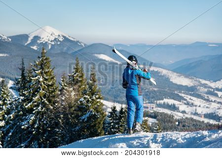 Rear View Of Female Skier Standing On Top Of A Mountain With Skis On The Shoulder, Stunning Scenery