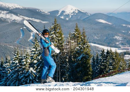 Female Skier Standing On Top Of A Hill Wearing Blue Ski Suit Mask And Black Helmet, Holding Skis On
