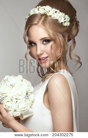 Portrait of a beautiful blond girl in image of the bride with white flowers on her head. Beauty face. Photo shot in the Studio on a grey background