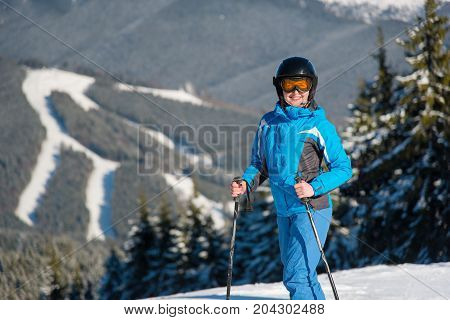 Shot Of A Female Skier Smiling To The Camera Joyfully While Skiing In The Mountain On A Sunny Winter
