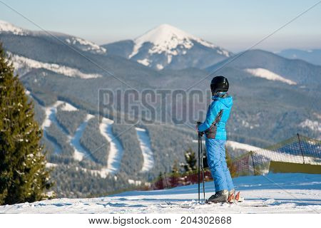 Shot Of A Woman Skier Looking Away, Enjoying Stunning Winter Mountains View, Forests, Ski Slopes On