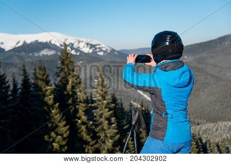 Rearview Shot Of A Female Skier Using Her Smart Phone Taking Photos Of Stunning Winter Scenery In Th