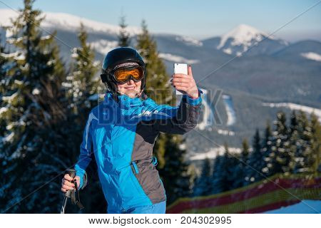 Close Up Portrait Of Woman Skier Smiling, Using Her Smart Phone Taking Photos Of Stunning Winter Sce