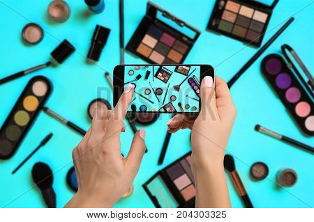 Young woman taking photo to cosmetics with cell phone or smartphone digital camera for post to sell online on the internet. Online business internet of things concept