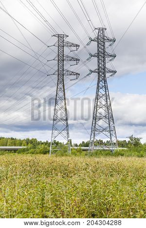 Two tall high voltage power line masts and cables in the field
