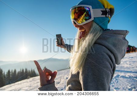 Female Snowboarder Enjoying Sunset After Snowboarding, Using Her Smart Phone, Taking Pictures Of Win