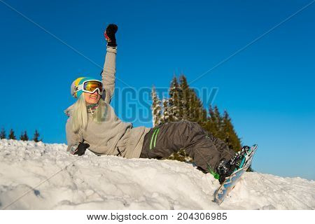 Low Angle Shot Of A Happy Girl Snowboarder Sitting On Top Of The Slope, Smiling And Relaxing Outdoor