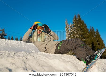 Low Angle Shot Of A Happy Young Woman Snowboarder Lying On Top Of The Slope, Relaxing Outdoors On Th