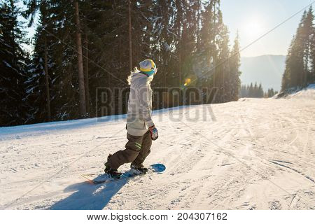 Female Snowboarder Riding The Slope At Winter Ski Resort In The Beautiful Evening, Enjoying Sunset