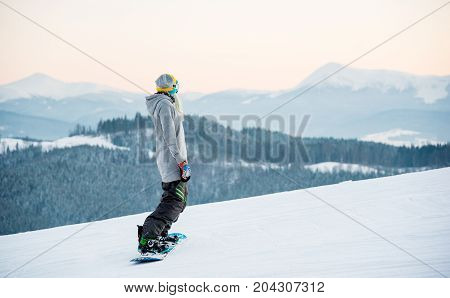 Female Snowboarder Enjoying Skiing In Mountains In The Evening On The Slope At Winter Ski Resort In