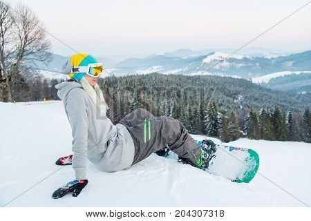 Shot Of A Cheerful Young Female Snowboarder Sitting On The Snow, Having Fun Outdoors, Resting In The