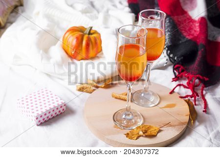 champagne pumpkin on a wooden board on a bed with a blanket and dry autumn leaves copy space
