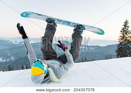 Excited Female Snowboarder Having Fun On The Slope Lying On The Snow With Her Legs In The Air In The