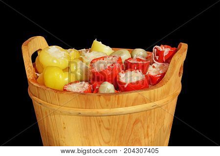 Pickled peppers stuffed with shredded cabbage in wooden pail over black background