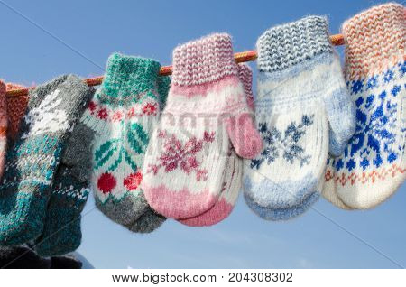 Mittens At Winter Christmas Market. A variety colorful knitted of woolen mittens hanging on a rope. Christmas gift or souvenir.