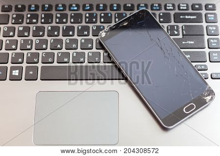 Broken smartphone with cracked screen lay on laptop