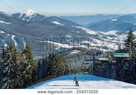 Skier Enjoying Skiing On Beautiful Sunny Winter Day. Mountains, Forests, Ski Slopes, Ski Resort On T