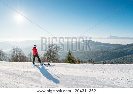 Rearview Shot Of A Man Skier Resting After The Ride Standing On Top Of The Ski Slope Looking Around