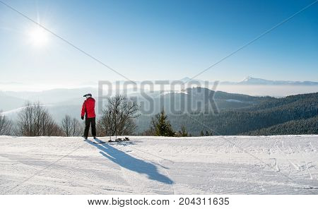 Rearview Shot Of A Skier Resting After The Ride Standing On Top Of The Ski Slope Looking Around Enjo