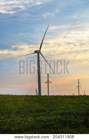 Windmill for electric power production on sunset background. Vertical shot.