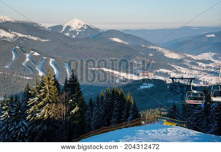 Winter Landscape In The Evening At Ski Resort. Blue Sky, Mountains, Forests, Slopes, Ski-lifts On Th
