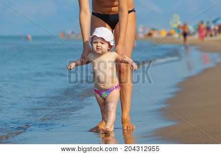 Mom Teaches Her Daughter To Walk To The Beach.