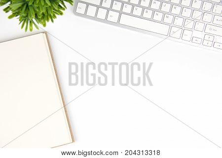 Copy space keyboard and blank book and plant top view high angle. white isolated background