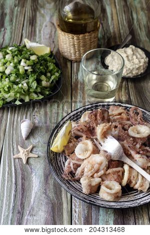 Fried calamari, salad, sauce and white wine on a wooden table closeup