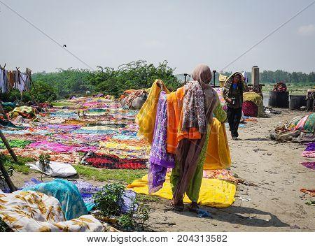 People Washing Cloth On The Sandy Banks