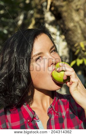 LATVIA, RIGA, SEPTEMBER, 19, 2015 - Portrait of cute young brunette in a checkered red shirt bites a fresh green apple. Riga, Latvia