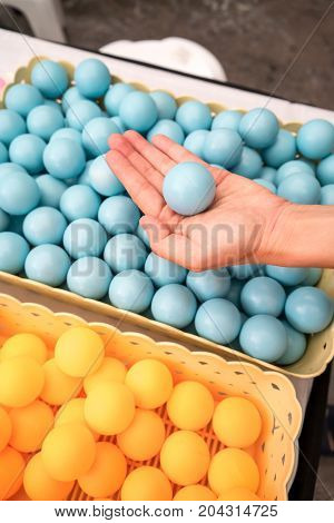 Woman hand holding one blue ping-pong balls.