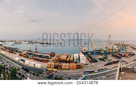ALBANIA DURRES - September 22 2015: Panorama of the cargo terminal of the international port of Durres at sunset. Unloading of the tanker by cargo cranes. A platform for storing sea freight containers. Cruise liners and cargo ships are moored in the port