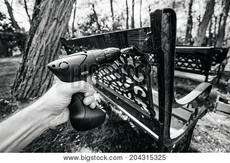 screwdriver in the hand of man screwing the screw into the detail of the bench. Repair of Park property. black and white photography