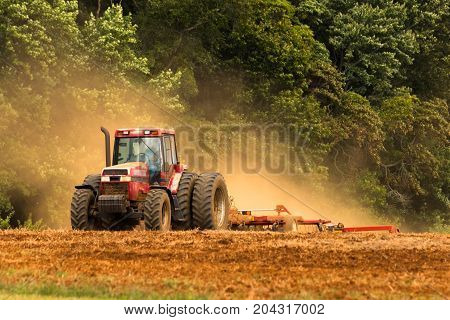A tractor kicks up a lot of dust while plowing a field.