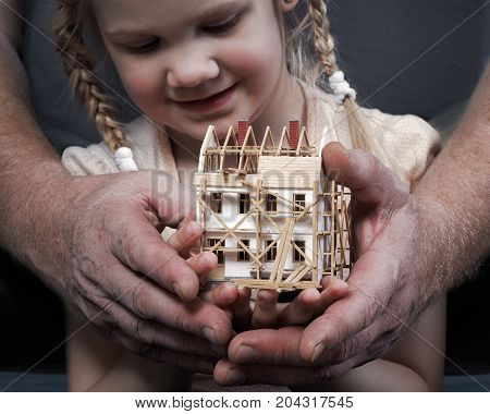 Men's hands show the little girl the layout of a house under construction