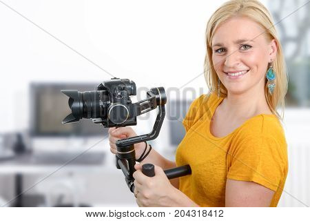 beautiful young woman videographer using steady cam