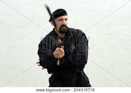 The security man in uniform is practicing martial arts with nunchaku on white background.