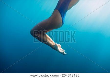 Slim woman with bikini in underwater. Blue ocean in Bali
