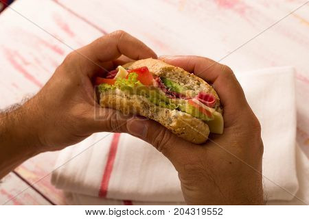 man holding a sandwich with small bite ,close-up